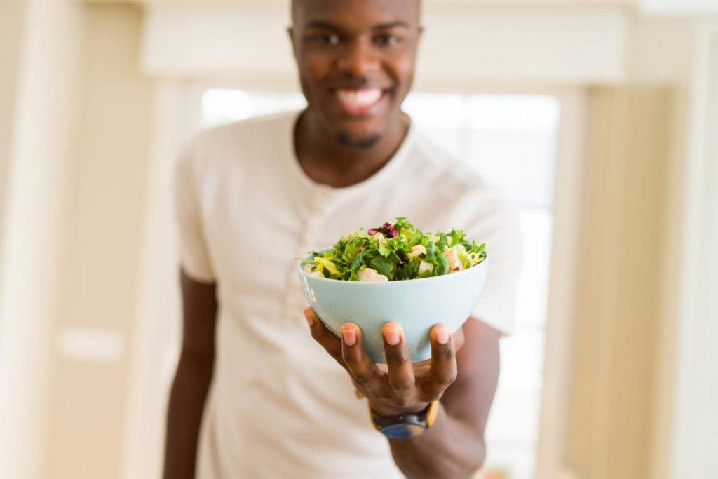 homem comendo vegetais